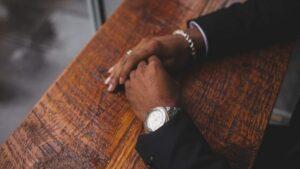 Mann mit Anzug und schicker Uhr sitzt an einem Holztisch