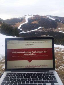 Macbook mit einer Webseite und Berge mit etwas Schnee im Hintergrund