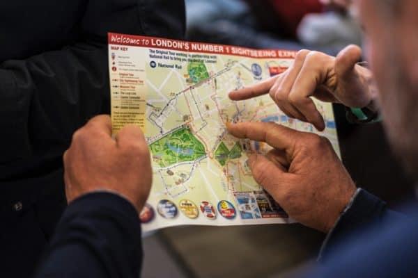 Männer zeigen mit Fingern auf einen Stadtplan